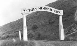 "White wooden arch with the words, ""Whitman Memorial Park."""