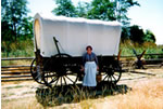 Woman in pioneer dress stands next to replica covered wagon