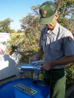 Park ranger standing next to drum filled with biodiesel.