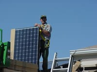 Park ranger stands on roof with solar panel that is as tall as his shoulder.