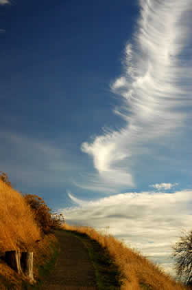 Wispy horsetail and cirrus clouds fill a blue sky above the trail leading to the top of the hill.