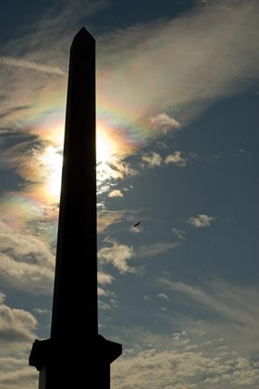 The Whitman Memorial Shaft is silhouetted against Iridescent clouds.