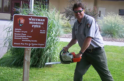 Park ranger uses chain saw to cut down fee sign.