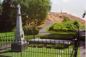 Gray memorial and Great Grave with trail to top of hill in background. Whitman memorial at top of hill.