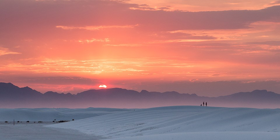The sun sets amidst a pink and orange sky above the dunes