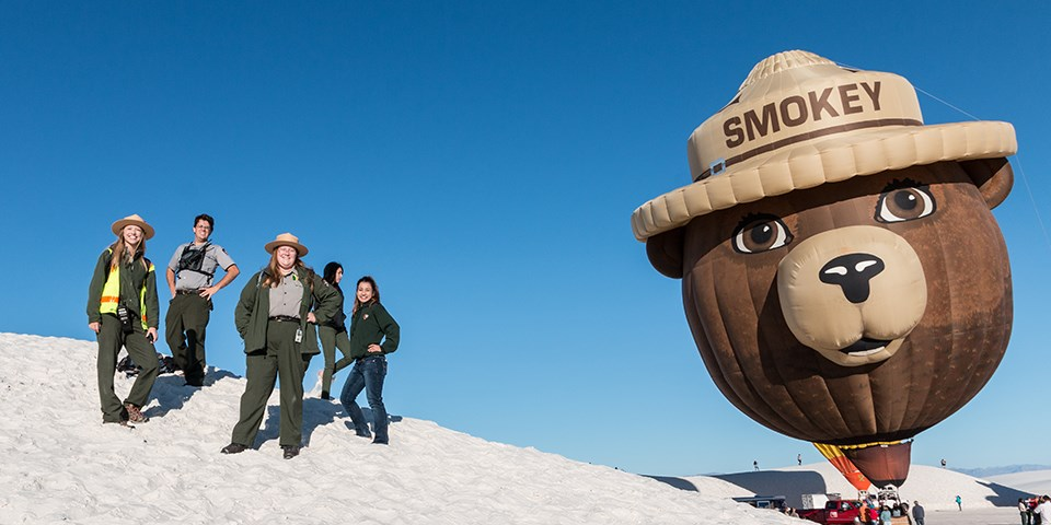A group of employees stand on a sand dune with a giant Smokey Bear hot air balloon in the background.