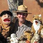 A man is surrounded by puppets and stuffed animals