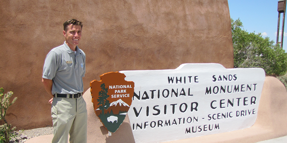 A teacher stands next to a park service arrowhead and visitor center sign.