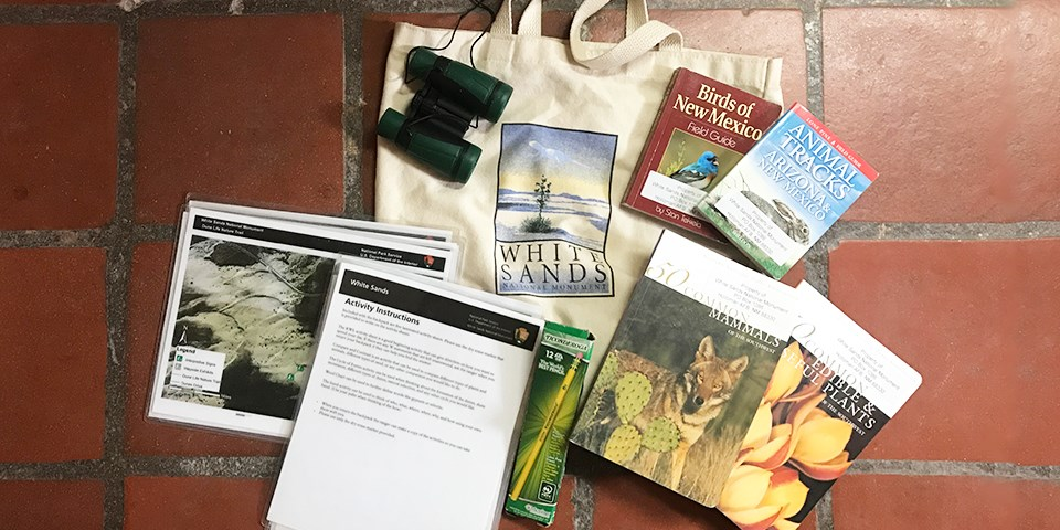 A bag surrounded by a collection of items, including books, binoculars, and laminated maps and instructions.