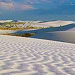 White sands with ripples and a blue sky.