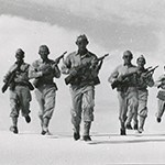 Army personnel marching on sand.