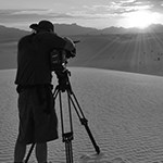 Photographer with tripod on dune.