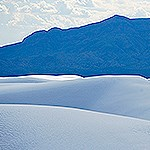 White sand dunes with mountains in the background.