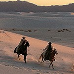 Two horseback riders in the dunefield with the San Andres Mountains on the background.