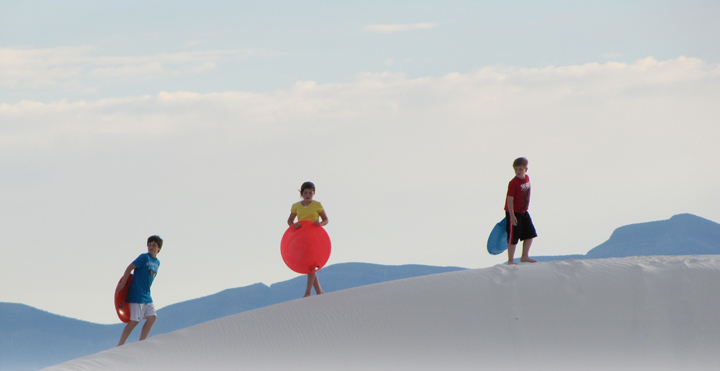 Kids sledding on the dunes