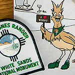 Riley the roadrunner next to a White Sands Junior Ranger patch.