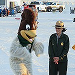 Riley the Roadrunner is dancing next to a park ranger