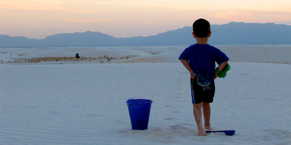 Child playing in the dunes with a sunset on the background.