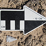 A black and white arrow in brown dirt to provide scale for the adjacent stone arrowhead