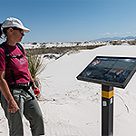 A woman looks at a trail sign in white sand dunes.
