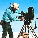 Man with large video camera on tripod in the dunes.