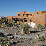 A brown adobe building with a graveled plant garden in front
