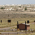 A brown building surrounded by green scrub and vegetated dunes