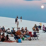 Visitors enjoying the dunes with a full moon on the background.
