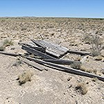 Old boards or pieces of a structure lying in arid scrub grassland
