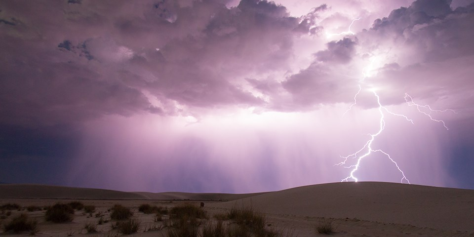 Lightning strikes amidst a bright purple sky and white sand dunes