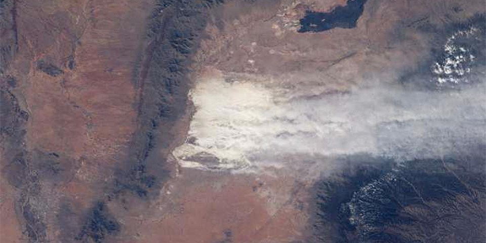 An image from space of white sand and dust being blown over a mountain range