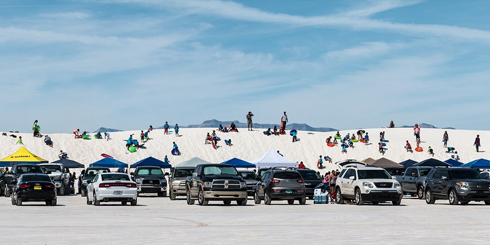 Vehicles parked in front of dunes covered with people