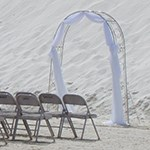 Arch with white fabric and chairs set up in front of dune.