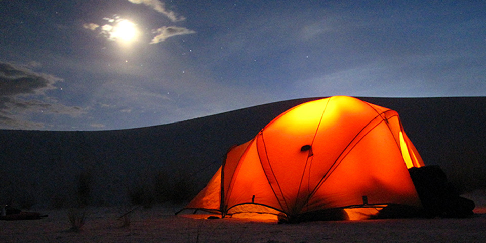Camping tent out in the backcountry camping loop with a full moon and a dune in the background.