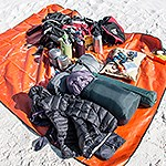 A pile of gear and hiking supplies spread on an orange tarp