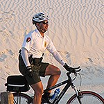 Law enforcement ranger rides bicycle in the dunes