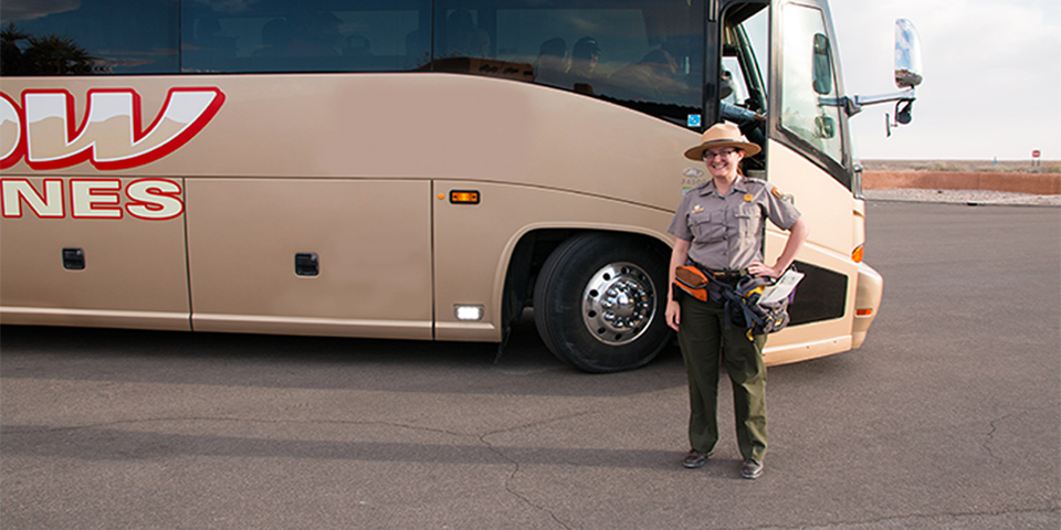 Park Ranger in front of a bronze colored commercial bus.