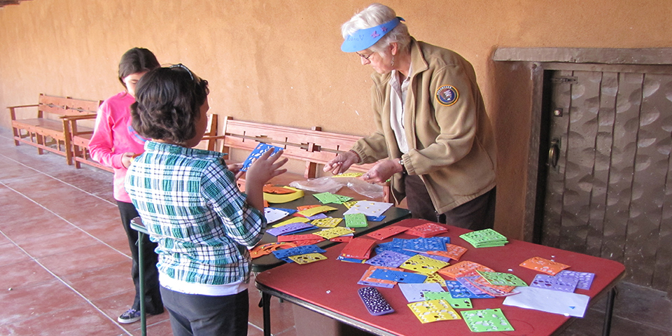 Visitors engaging with a volunteer for a crafty kids program.