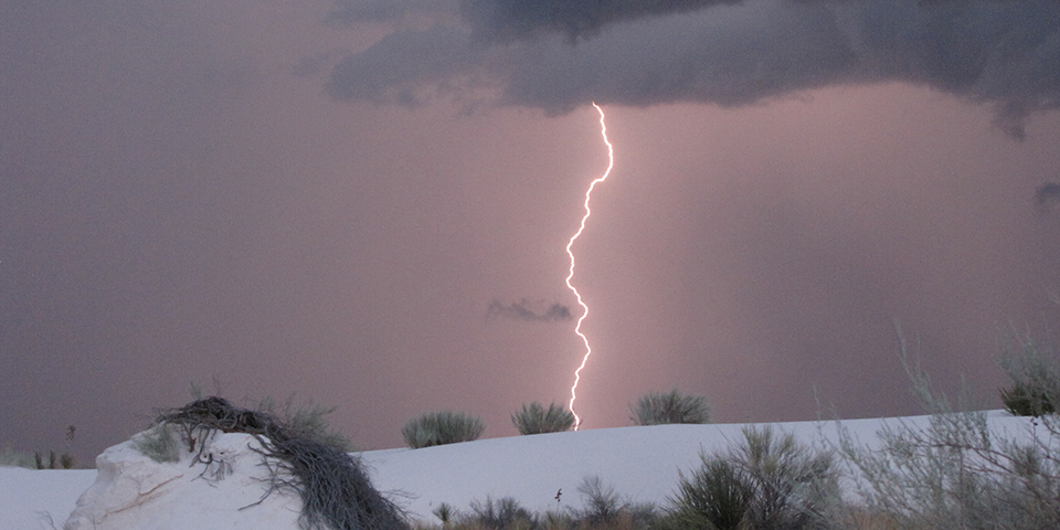 Pink sky with a bright lightning bolt hitting the white sand