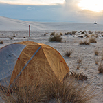Orange and gray tent set up in area with white sand and grasses
