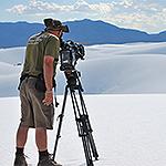Man with camera on tripod filming dunes.