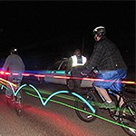 Bicyclers with bright lights passing quickly by in the dark
