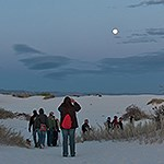 A group of visitors walking under a full moon sky