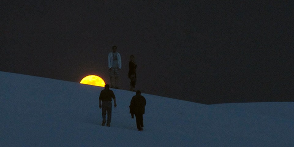 Visitors hiking on the dunes with a full moon on the background.