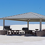 Group use area with a roof, picnic tables, grills, and trash cans.