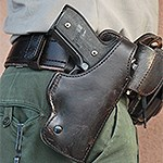 Firearm in leather case attached to belt