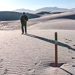 Man hiking on white sand dunes