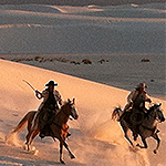 Two riders on horses galloping through sand