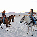 Two visitors horseback riding in the dunefield.