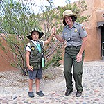Junior ranger high fiving a park ranger.